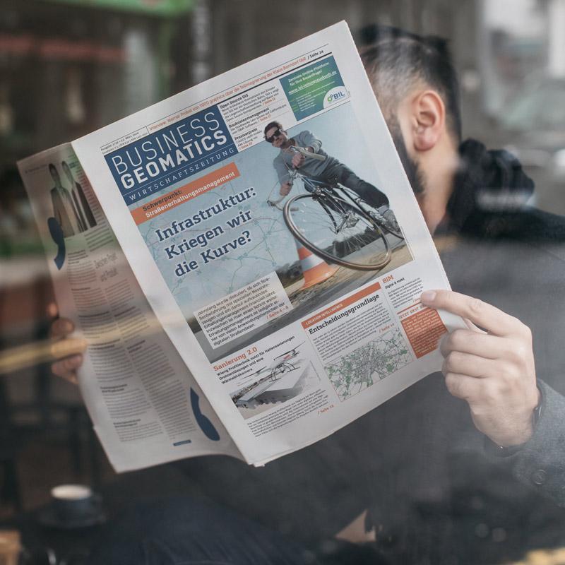 Mann liest in einem Cafe eine Zeitschrift